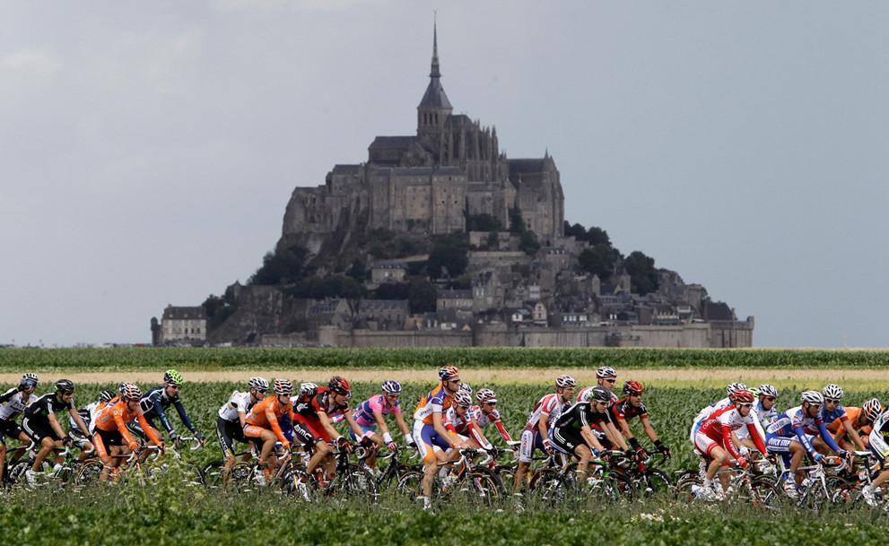 Участники велосипедной гонки мира Франс де Тур на фоне горы Мон-Сен-Мишель (гора Архангела Михаила)
